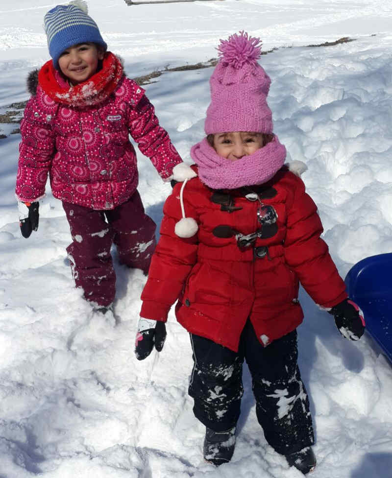Two young girls dressed in warm winter gear smiling with background of snow